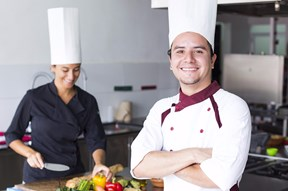 a man and a woman in a kitchen, both smiling and wearing chef hats